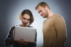 Hombre sorprendido y adolescente que se pregunta que miran el ordenador portátil Fotografía de archivo libre de regalías