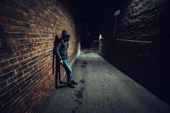 Hombre sospechoso en el callejón oscuro que espera algo foto de archivo libre de regalías