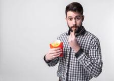 Hombre sosteniendo las patatas fritas el estudiante come los alimentos de preparación rápida comida no útil individuo muy hambrie Imagen de archivo libre de regalías