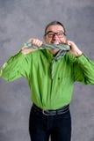 Hombre subrayado en camisa y vidrios verdes que muerde en su corbata Foto de archivo