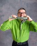 Hombre subrayado en camisa y vidrios verdes que muerde en su corbata Foto de archivo libre de regalías