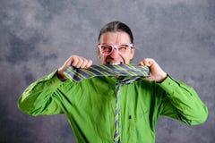 Hombre subrayado en vidrios verdes del rosa de la camisa que muerde en su corbata Fotografía de archivo libre de regalías