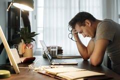 Hombre subrayado mientras que trabaja en el ordenador portátil Fotografía de archivo libre de regalías
