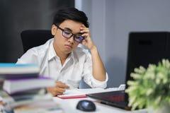 Hombre subrayado que estudia con el libro y el ordenador portátil Imagen de archivo libre de regalías