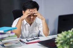 Hombre subrayado que estudia con el libro y el ordenador portátil Imágenes de archivo libres de regalías