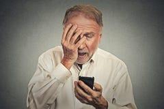 Hombre subrayado que sostiene el teléfono móvil chocado con el mensaje recibido Foto de archivo libre de regalías
