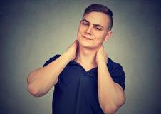 Hombre subrayado que tiene dolor en cuello imagenes de archivo
