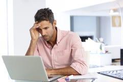 Hombre subrayado que trabaja en el ordenador portátil en Ministerio del Interior Imagen de archivo