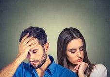 Hombre subrayado y mujer jovenes tristes de los pares que miran abajo fotos de archivo