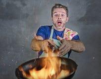 Hombre sucio chocado con el delantal que sostiene la cacerola en el fuego que quema la comida en desastre de la cocina y terrible imágenes de archivo libres de regalías