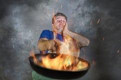 Hombre sucio chocado con el delantal que sostiene la cacerola en el fuego que quema la comida en desastre de la cocina y terrible imagen de archivo libre de regalías
