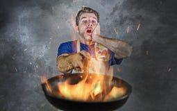 Hombre sucio chocado con el delantal que sostiene la cacerola en el fuego que quema la comida en desastre de la cocina y terrible imagen de archivo