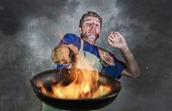 Hombre sucio chocado con el delantal que sostiene la cacerola en el fuego que quema la comida en desastre de la cocina y terrible imagenes de archivo