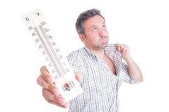 Hombre sudoroso que sostiene el termómetro como concepto del calor del verano Fotos de archivo