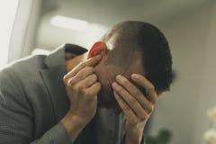 Hombre sufridor con sus manos en su cabeza Imagen de archivo libre de regalías
