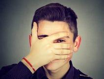 Hombre tímido que mira a escondidas a través de sus fingeres Imagenes de archivo