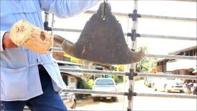 Hombre tailandés que bate un gongo o una campana budista tradicional mientras que en un camión como parte de una procesión que ll almacen de video