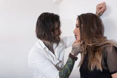 Hombre tatuado atractivo que se acerca y que toca a una mujer joven Foto de archivo