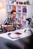 Hombre tatuado comunicativo con el reloj rojo que se sienta en la tabla imágenes de archivo libres de regalías