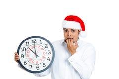 Hombre tensado en el sombrero de santa que sostiene el reloj fotos de archivo