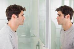 Hombre tensado que mira a uno mismo en espejo del cuarto de baño Fotos de archivo