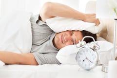 Hombre tensionado que mira su sonido del reloj de alarma Imagen de archivo libre de regalías