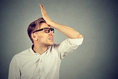 Hombre tonto que da una palmada a la mano en la cabeza que tiene duh momento imagenes de archivo