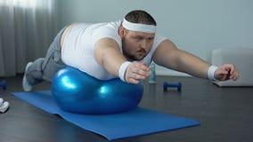 Hombre trabajador obeso que practica el ejercicio estático, programa de entrenamiento de la fuerza almacen de video