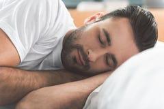 Hombre tranquilo que disfruta de sueños mientras que miente en cama Foto de archivo