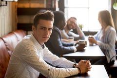 Hombre trastornado celoso de los amigos multirraciales que se divierten en café fotografía de archivo