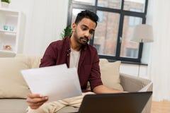 Hombre trastornado con el ordenador portátil y los papeles en casa imagenes de archivo