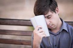 Hombre trastornado con la biblia en el banco Fotos de archivo