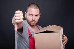 Hombre trastornado del motor que sostiene la caja que muestra el pulgar abajo Imagenes de archivo