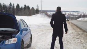 Hombre trastornado joven que golpea la rueda con el pie de su coche quebrado en carretera nacional del invierno almacen de video