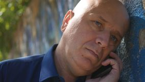 Hombre triste cerca de una pared en el intento de la calle para iniciar una llamada de teléfono foto de archivo libre de regalías