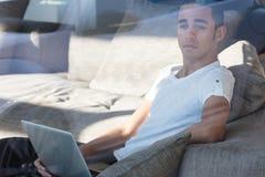 Hombre triste con el ordenador portátil que mira lejos Fotografía de archivo libre de regalías