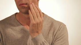 Hombre triste en dolor que da masajes a su mejilla Retrato de un hombre en el fondo blanco Dolor de muelas almacen de video