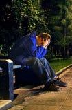 Hombre triste en el parque de la noche Imagenes de archivo