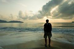 Hombre triste en el tiempo del amanecer en la playa Imagen de archivo libre de regalías