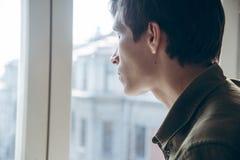 Hombre triste joven que mira hacia fuera la ventana Fotos de archivo libres de regalías