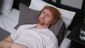 Hombre triste que miente en la cama que siente incómoda, malestar imagen de archivo