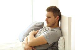 Hombre triste que mira lejos en la cama Imagen de archivo libre de regalías