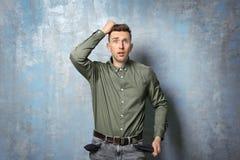 Hombre triste que muestra sus bolsillos vacíos Fotografía de archivo libre de regalías