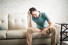 Hombre triste que piensa en la sala de estar Imagen de archivo