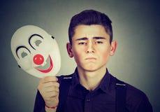 Hombre triste que saca la máscara feliz del payaso Doble personalidad Foto de archivo libre de regalías