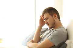 Hombre triste que se lamenta en la cama Fotografía de archivo libre de regalías