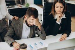 Hombre triste que se sienta en el escritorio en la oficina que mira la pantalla del ordenador portátil que tiene problema, malas  fotos de archivo libres de regalías