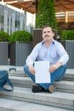 Hombre triste que se sienta en los pasos con una muestra vacía de la maleta Fotos de archivo libres de regalías