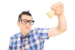 Hombre triste que sostiene un cono de helado vacío foto de archivo