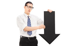 Hombre triste que sostiene una flecha negra grande que señala abajo Fotografía de archivo libre de regalías